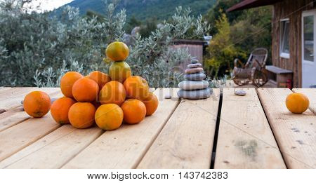 Heap of Orange Fruits and Column of Stone Pebbles on wood Floor rural Scene