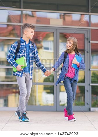 Happy children - boy and girl with books and backpacks on the first school day. Young students beginning of class after vacation. Full length outdoor portrait in yard.