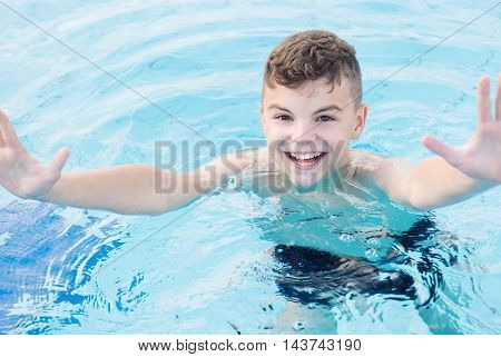 Close-up portrait of happy teen boy in the swimming pool at aquapark. Cute child having fun enjoyable time on vacation. Looking at camera.