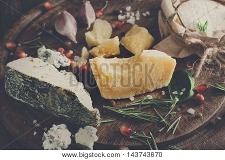 Cheese delikatessen closeup on rustic wood. Wooden desk with blue cheese roquefort, parmesan, camembert and brie cuts decorated with garlic, pomegranate and rosemary. Soft toned candid image