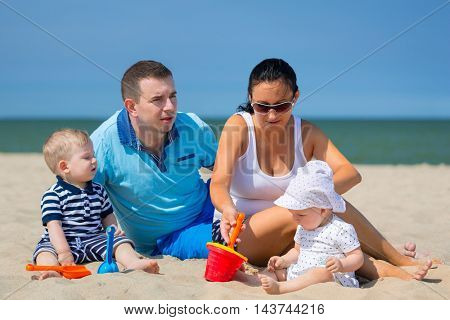 Family with twins on sun holidays at the beach
