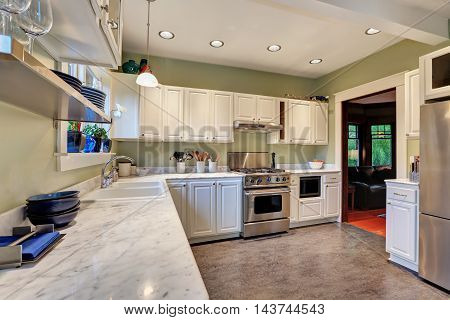 Bright Kitchen Interior With White Cabinets And Marble Counter Top