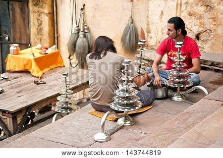 Varanasi, Uttar Pradesh, India - July 30, 2011: Unidentified Hindu pilgrims preparing candlesticks for the Ganga Aarti ritual. Puja is a Hindu ritual that takes place at Triveni Ghat on the banks of the river Ganges