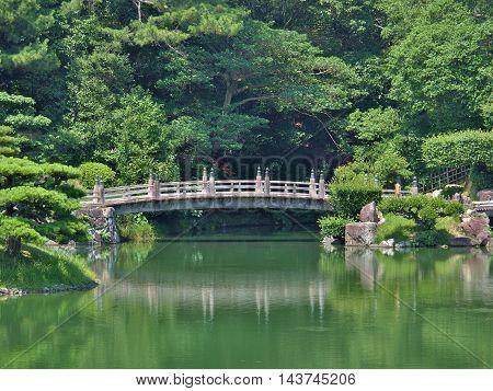 A wooden bridge in Ritsurin Garden in Takamatsu city, Kagawa Prefecture, Japan. Ritsurin Garden is one of the most famous historical gardens in Japan.
