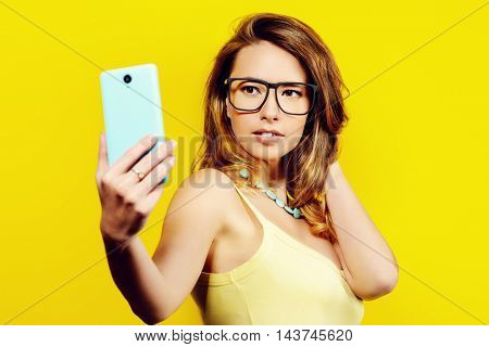 Pretty young woman makes selfie on her smartphone. Bright summer style. Beauty, fashion.