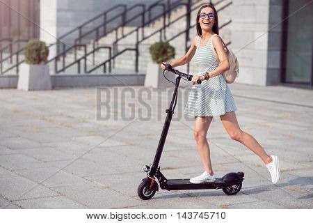 Can not hide emotions. Joyful delighted woman riding a kick scooter and smiling while resting