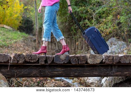 Person walking on old wooden bridge pulling Travel Suitcase female Legs and Hand casual vacation Clothing red attractive high Heels Shoes and Jeans