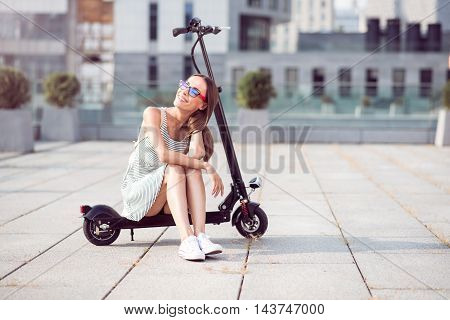Have a break. Joyful beautiful woman smiling and sitting on the kick scooter while resting