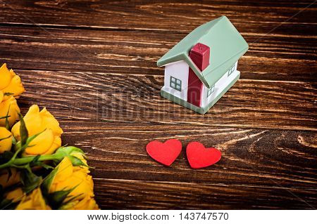 Yellow roses with house model and heart over wooden table.