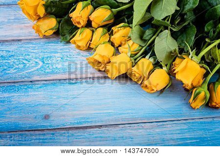 Yellow roses over blue rustic wooden table.
