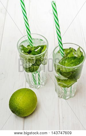 Summer drink mojito drink with ice mint and lime on wooden table