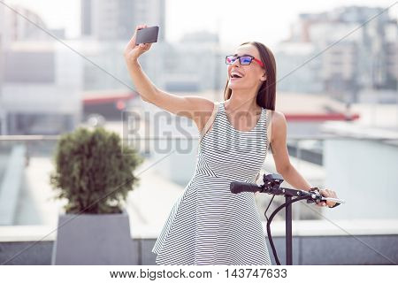 Full of gladness. Positive delighted smiling woman holding kick scooter and expressing joy while making selfies