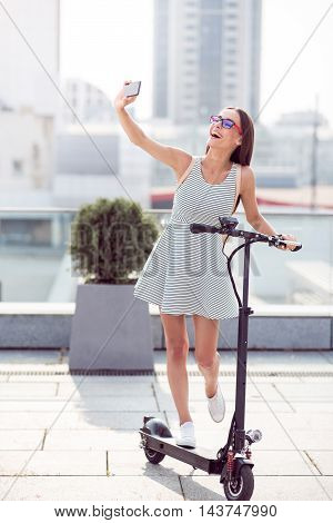 Leave it in memory. Positive content charming woman holding kick scooter and smiling while making selfies
