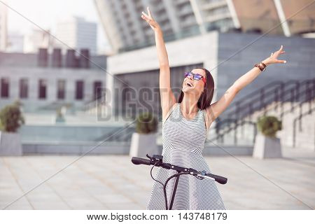 Express yourself. Overjoyed delighted woman smiling and holding hands up while riding a kick scooter