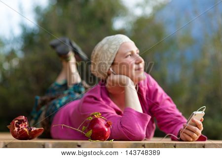 Portrait of Cute Woman serene inspired face holding Telephone listening Music earphones green Forest and Mountains on Background Focus on fresh Pomegranates
