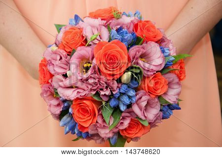 Wedding bouquet in hands of the bride against the background of a wedding dress