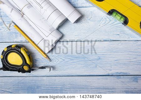 Architect worplace top view. Architectural project, blueprints, blueprint rolls on wooden desk table. Construction background. Engineering tools. Copy space