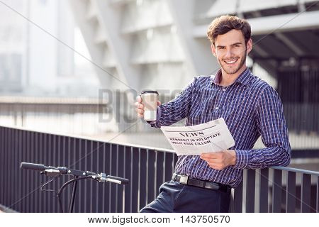 Get energized. Positive content handsome man drinking coffee and holding newspaper while expressing joy