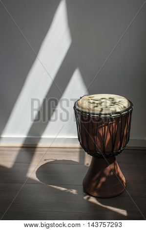 One drum in the sunlight in the room on the floor
