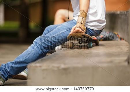 Outdors image of guy sitting on skateboard wearing sports protection on hand