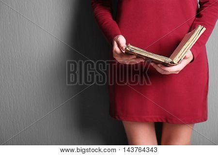 Woman holding old book on gray background