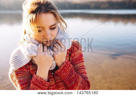Sad hipster girl feeling cold alone at a lake. Alone teenage girl in a cold weather.