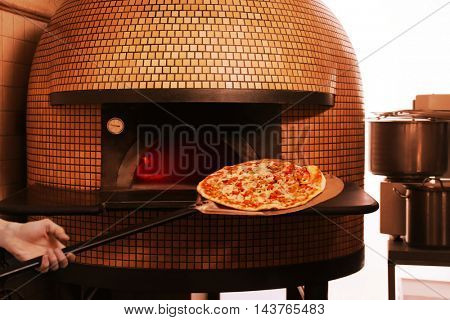 Man putting pizza in wood-burning stove
