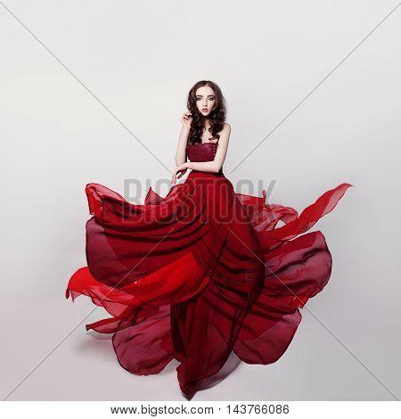 Beautiful Woman Wearing Romantic Red Dress on gray background