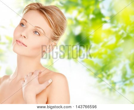 beauty, people and bodycare concept -beautiful young woman face and hands over green natural background