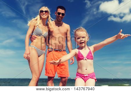 family, childhood, travel and people concept - close up of happy man, woman and little girl having fun on summer beach