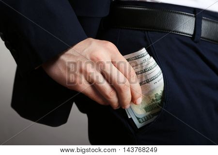Businessman putting banknotes in pocket. Corruption concept