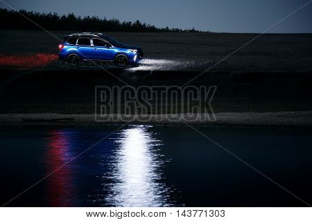 Saratov, Russia - September 28, 2015: Car Subaru Forester stand at countryside off-road and reflected on water at night