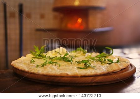 Tasty pizza on the table against wood-burning stove