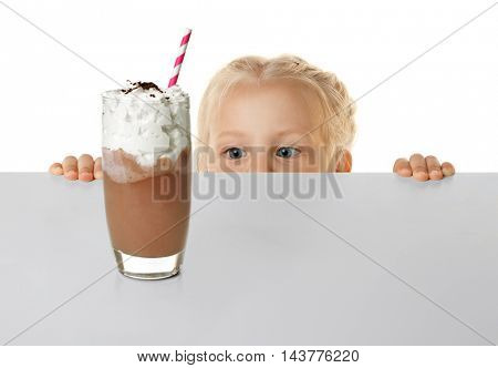 Funny little girl hiding behind white table and looking at glass of chocolate milk