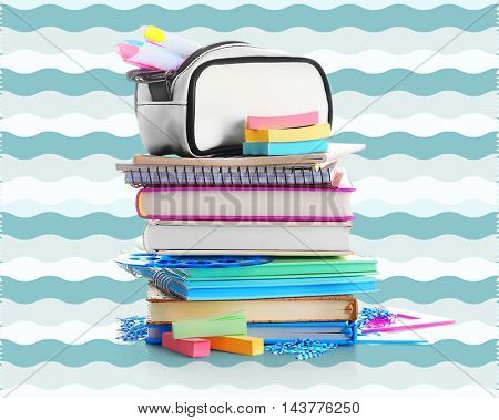 Stack of books and notebooks with colorful stationery on color background. School concept.