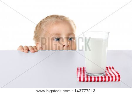 Funny little girl hiding behind white table and looking at glass of milk