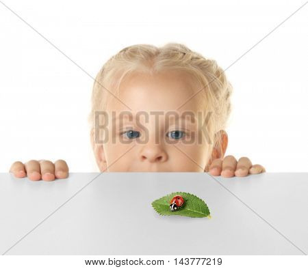 Funny little girl hiding behind white table and looking at ladybug on green leaf