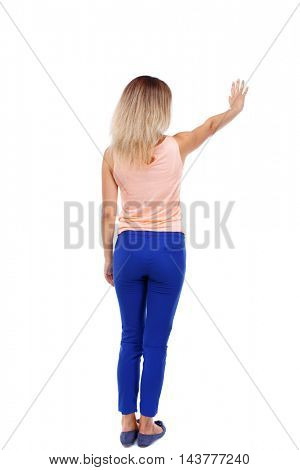 Back view of beautiful woman welcomes. Young teenager girl in jeans hand waving from. Rear view  people collection.  backside view of person.  Isolated over white background. Blonde in blue pants