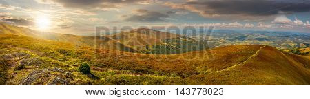 panoramic summer landscape under blue sky with clouds. Path through hillside meadow on Borzhava mountain ridge in Carpathians in evening light