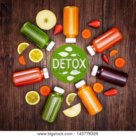 Bottles with delicious detox drinks and text detox on wooden background. Detox diet concept.