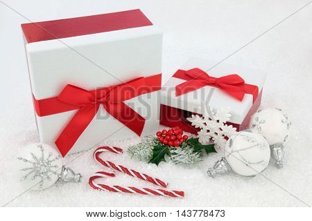 Christmas glitter gift boxes with red bows, candy canes, holly, fir and white snowflake bauble decorations on snow background.