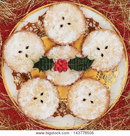 Christmas mince pie cakes with holly berries on a doilie and white plate with gold decorative strands.