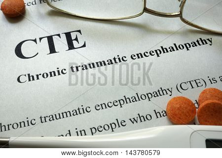Paper with words CTE, Chronic Traumatic Encephalopathy  and glasses. Medical concept.