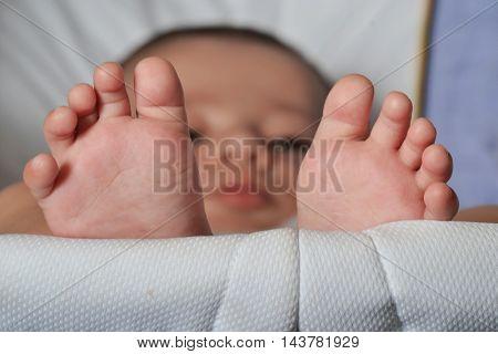 Little baby feet portrait lying down on baby trolley.