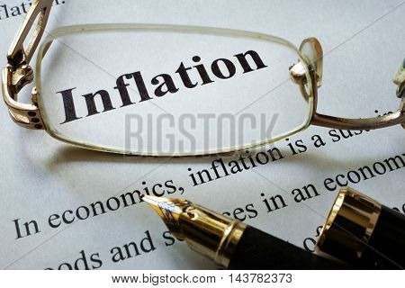 Paper with word inflation and glasses. Economic concept.