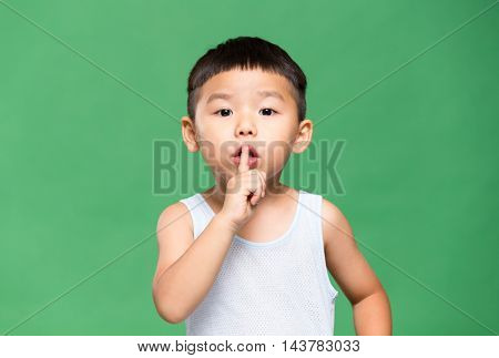 Little boy making a gesture for keeping quiet