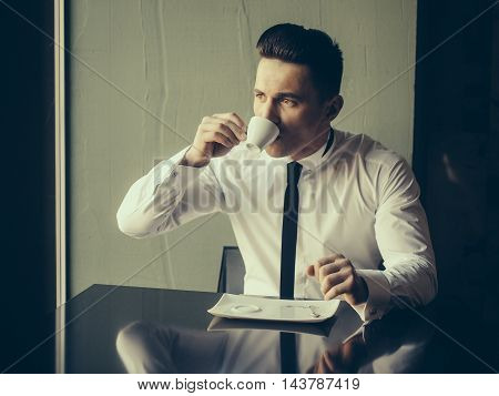 Man young handsome elegant model wears white shirt black skinny necktie sits at table drinks coffee and looks away indoor on grey background