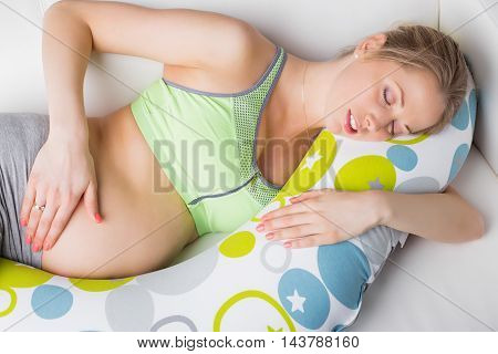 Pregnant woman sleeping on the pillow made for pregnant women