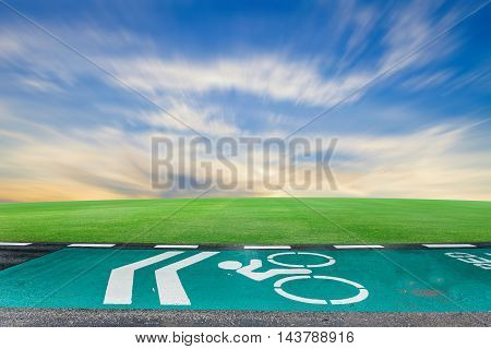 Green bicycle lanes on the asphalt roadBicycle symbol on street bike lane road for bicycles with green grass blue sky background in raining day