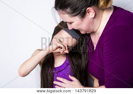A mother comforting her daughter in studio white background
